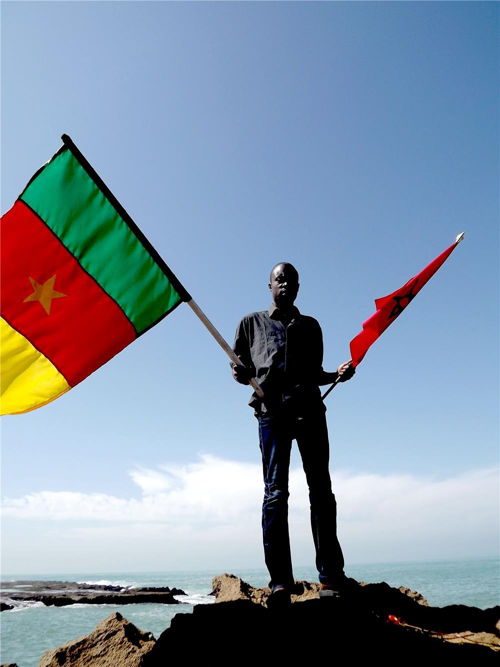 Ein unbegleiteter Minderjähriger aus Kamerun, dessen Reise nach Europa an der Nordküste Marokkos endete. In den Händen hält er die Nationalflaggen von Marokko und Kamerun.